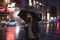 Man walking in city at night, using umbrella, Downtown, San Francisco, California, USA — Stock Photo