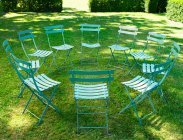 Circle of chairs on green grass in backyard — Stock Photo