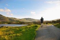 Visão traseira do homem que corre na estrada rural — Fotografia de Stock