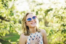 Head and shoulders of young woman wearing sunglasses, hand on chest looking at camera laughing — Stock Photo