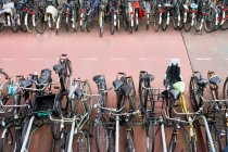 Велосипеды припаркованный в ряд на дороге, Амстердам, Нидерланды — стоковое фото