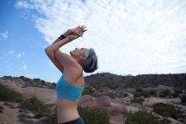 Visão lateral da mulher fazendo ioga no Vazquez Rocks, LA — Fotografia de Stock