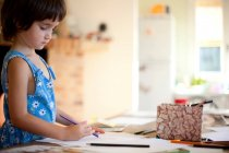Little girl drawing at kitchen table — Stock Photo