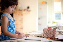 Bambina che disegna al tavolo della cucina — Foto stock
