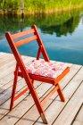Chair on wooden pier beside lake in sunlight — Stock Photo
