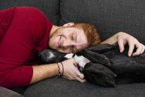 Young man lying on sofa hugging pet dog eyes closed smiling — Stock Photo