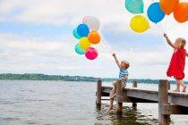 Bambini che tengono palloncini su un molo di legno — Foto stock