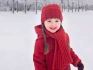 Smiling girl playing in snow — Stock Photo