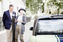 Ehepaar lädt Elektroauto auf Straße — Stockfoto