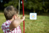 Rear view of teenage boy practicing archery — Stock Photo