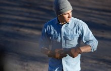 Человек снимает перчатки на улице — стоковое фото