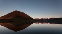 Sky and mountains reflected in lake — Stock Photo