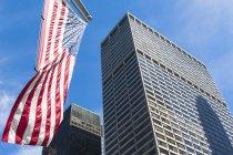 Inquadratura dal basso di grattacieli e noi bandiera, Manhattan, New York, Stati Uniti — Foto stock