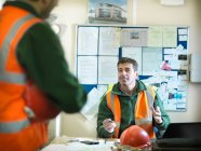 Capataz del sitio asesorando a aprendiz en la oficina del sitio de construcción - foto de stock