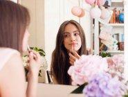Женщина наносит макияж в зеркало — стоковое фото