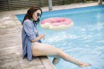 Donna seduta a bordo piscina spruzzi d'acqua con i piedi, Amagansett, New York, Stati Uniti d'America — Foto stock