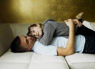 Padre e hija relajándose en el sofá - foto de stock