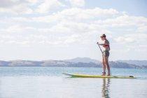 Середині дорослу жінку встати на морі paddleboarding — стокове фото