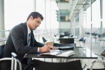 Uomo d'affari che prende appunti nel caffè — Foto stock