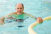 Older man swimming in pool — Stock Photo