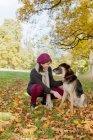 Donna sorridente che accarezza il cane nel parco in autunno — Foto stock