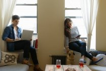 Young couple sitting on window sill using laptop and smartphone — Stock Photo