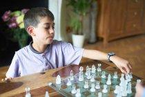 Junge spielt Schach im Wohnzimmer — Stockfoto