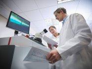 Scientifiques masculins et féminins à la machine de soudage laser en laboratoire, tenant des notes — Photo de stock