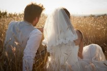 Newlywed couple sitting in tall grass — Stock Photo