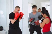 Trainer working with boxers in gym — Stock Photo
