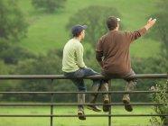 Fazendeiro conversando com filho no portão — Fotografia de Stock