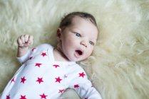 Bambino appena nato sdraiato su una coperta soffice guardando altrove — Foto stock