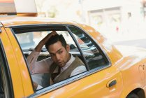 Worried businessman looking out of yellow cab window — Stock Photo