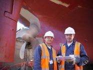 Travailleurs à côté de dessous de navire en cale sèche — Photo de stock