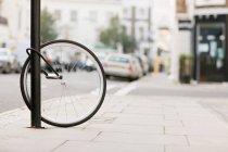 Ruota di bicicletta singolo assicurato al lampione — Foto stock