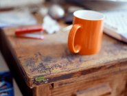 Graffiti and orange cup on wooden desk — Stock Photo
