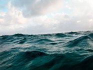 Ocean wave water surface with cloudy sky — Stock Photo