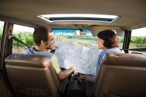Young couple in vehicle with map — Stock Photo