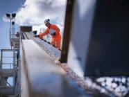 Работник, стоящий у каменосека и дробилки в карьере — стоковое фото