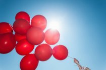 Hands holding bunch of red balloons against blue sky — Stock Photo