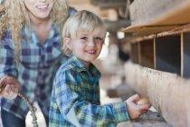 Ragazzo che raccoglie uova dalle galline — Foto stock