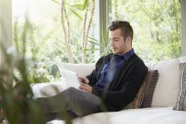 Man relaxing on sofa with feet up looking at digital tablet — Stock Photo