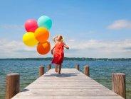 Ragazza che tiene i palloni sul pilastro di legno — Foto stock
