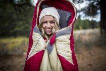 Retrato de mulher jovem vestindo malha chapéu envolvida em saco de dormir, Lake Tahoe, Nevada, EUA — Fotografia de Stock