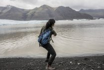 Rear view of female tourist skimming stones in sea,  Skaftafell, Iceland — Stock Photo