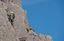Mise à l'échelle de paroi rocheuse abrupte de grimpeur — Photo de stock