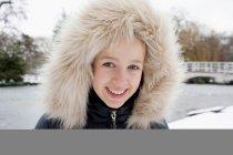 Fille souriante portant capuche en fourrure dans la neige — Photo de stock