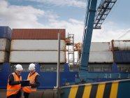 Travailleurs portuaires devant navire chargé — Photo de stock
