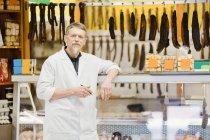 Carniceiro em pé no balcão de carne — Fotografia de Stock