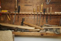 Closeup view of chisels and wood on workbench — Stock Photo